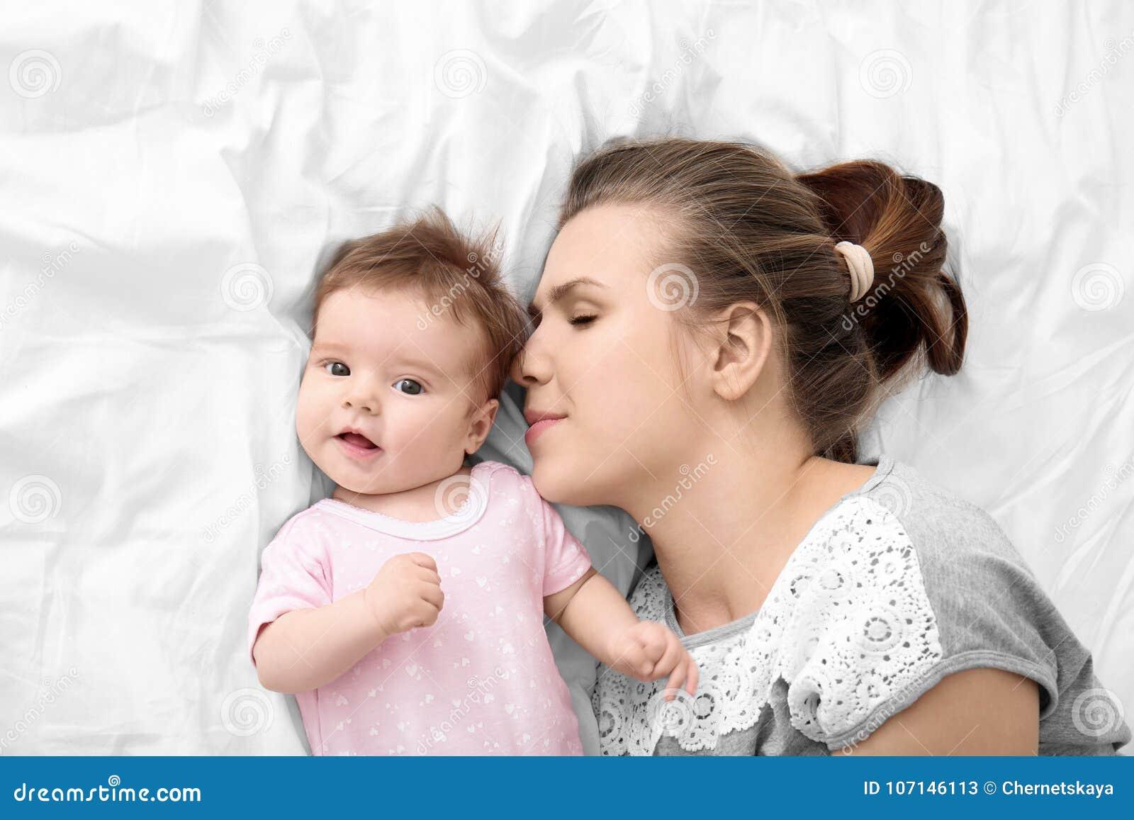 Jeune mère et bébé mignon sur le lit