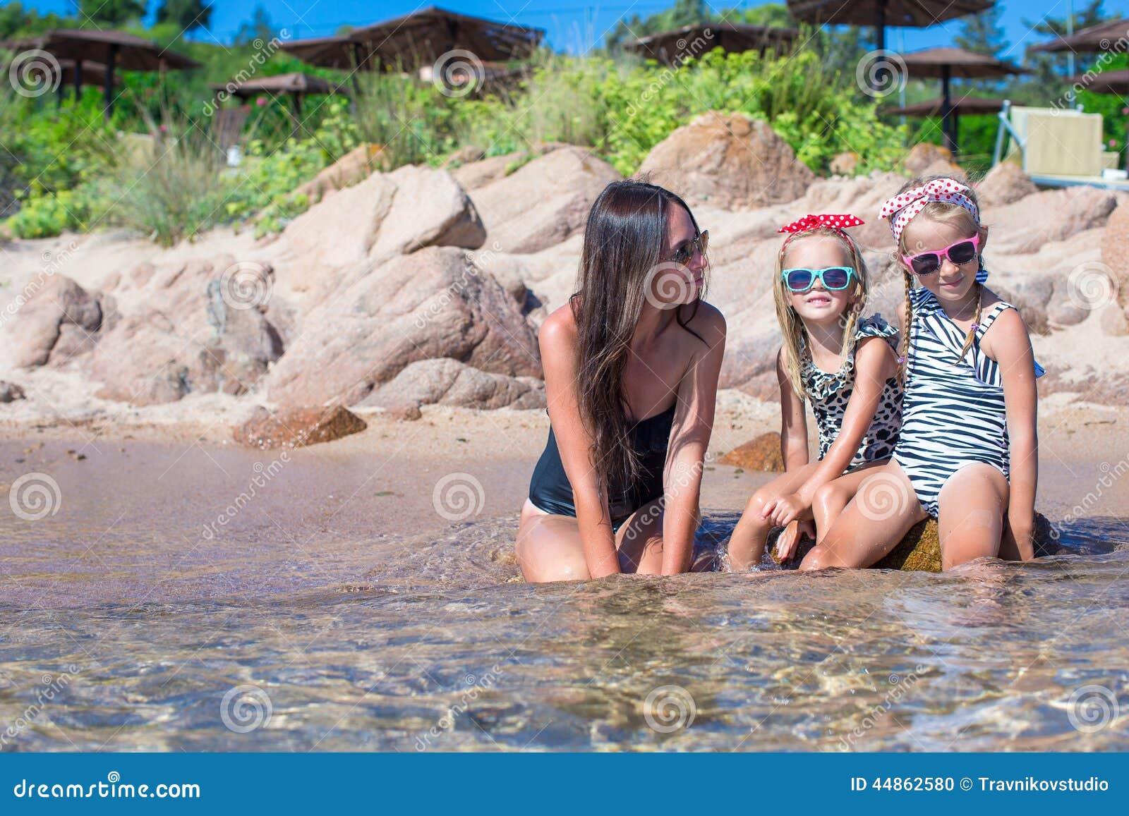 Jeune mère et deux ses enfants à la plage exotique dessus