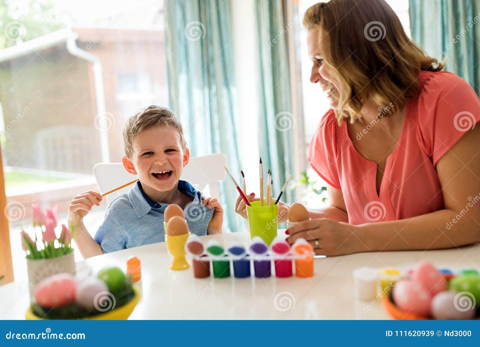 Jeune mère et son fils ayant l amusement tandis que la peinture eggs pour Pâques