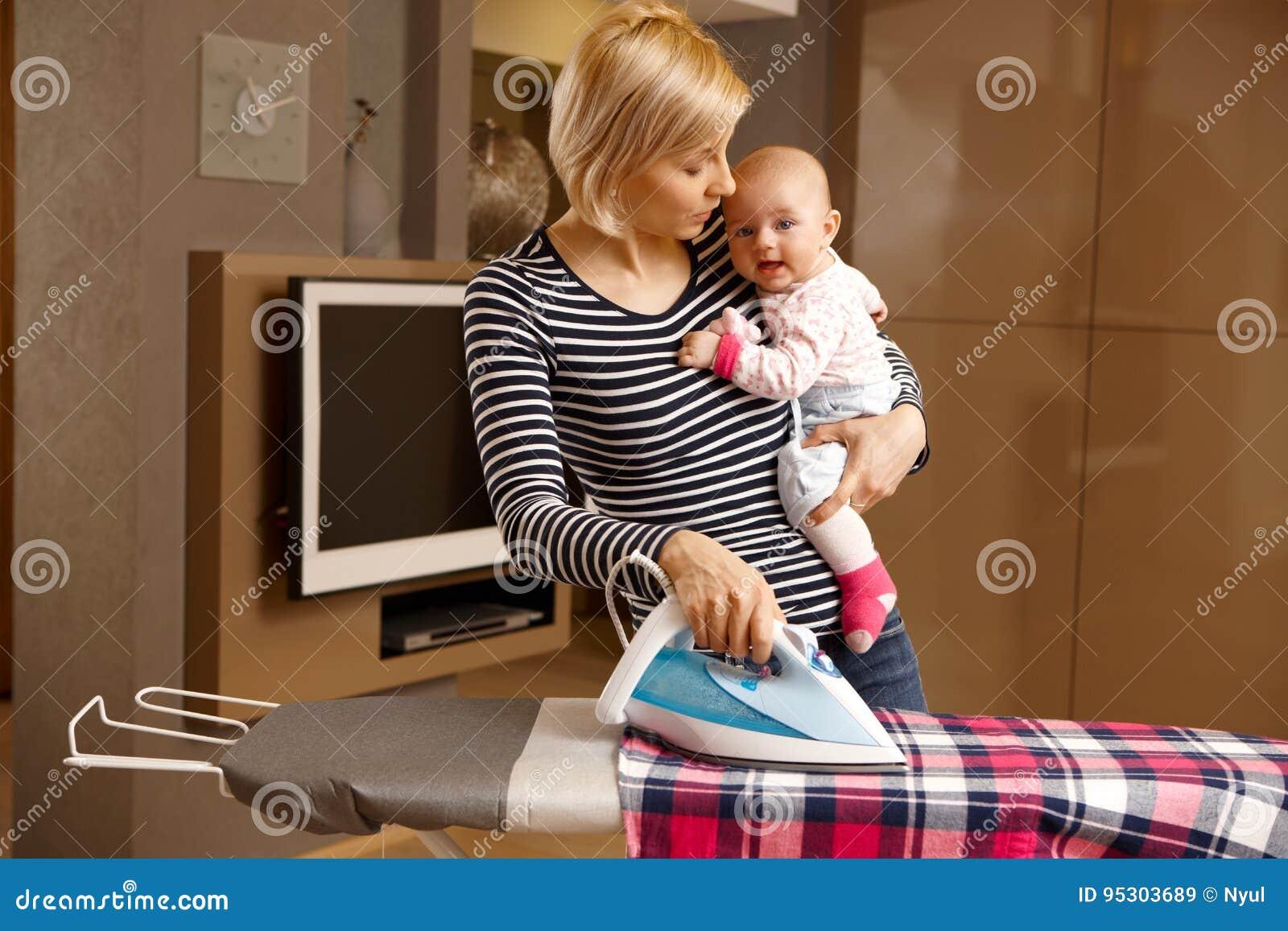 Jeune mère repassant avec le bébé dans le bras