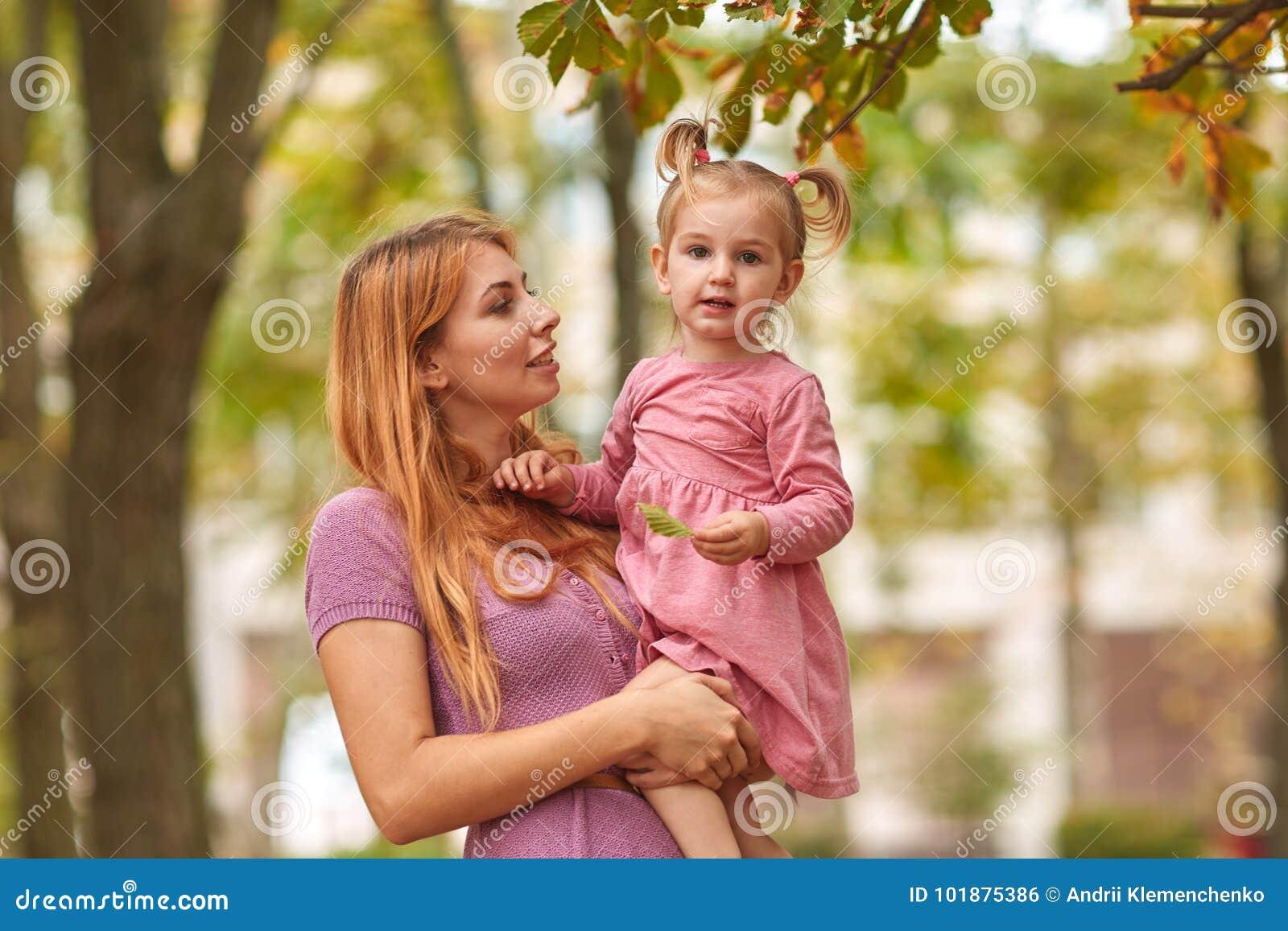 Jeune mère sur une promenade avec la fille et la feuille dans des mains