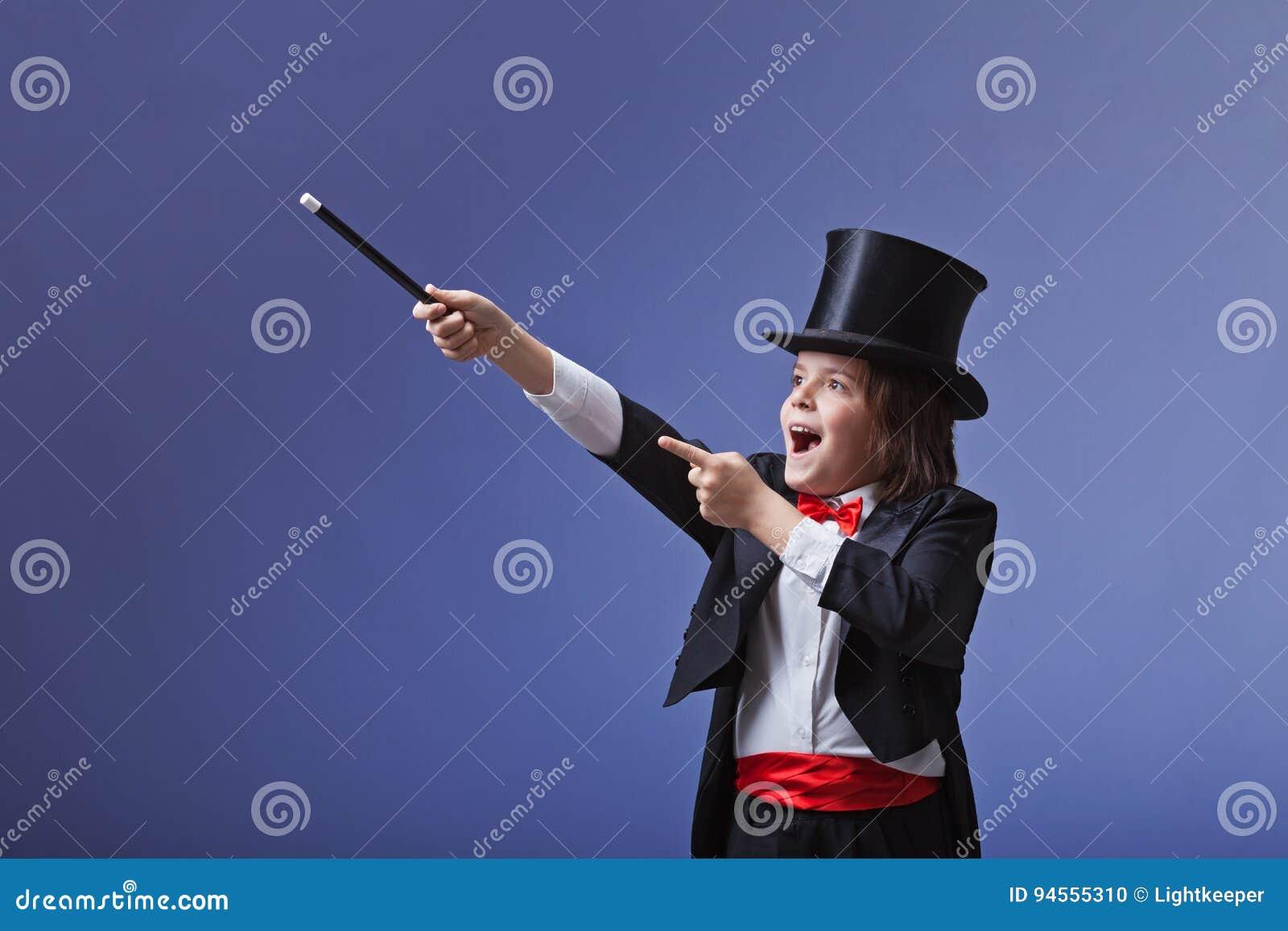 Jeune magicien exécutant avec une baguette magique magique