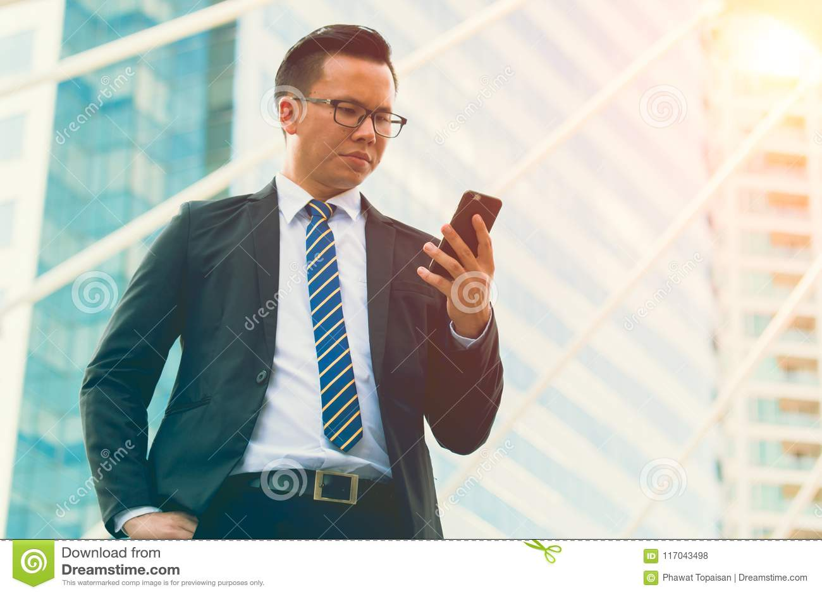 Jeune main moderne de costume de noir d usage d homme d affaires tenant le smartphone Bureau extérieur debout professionnel d hom