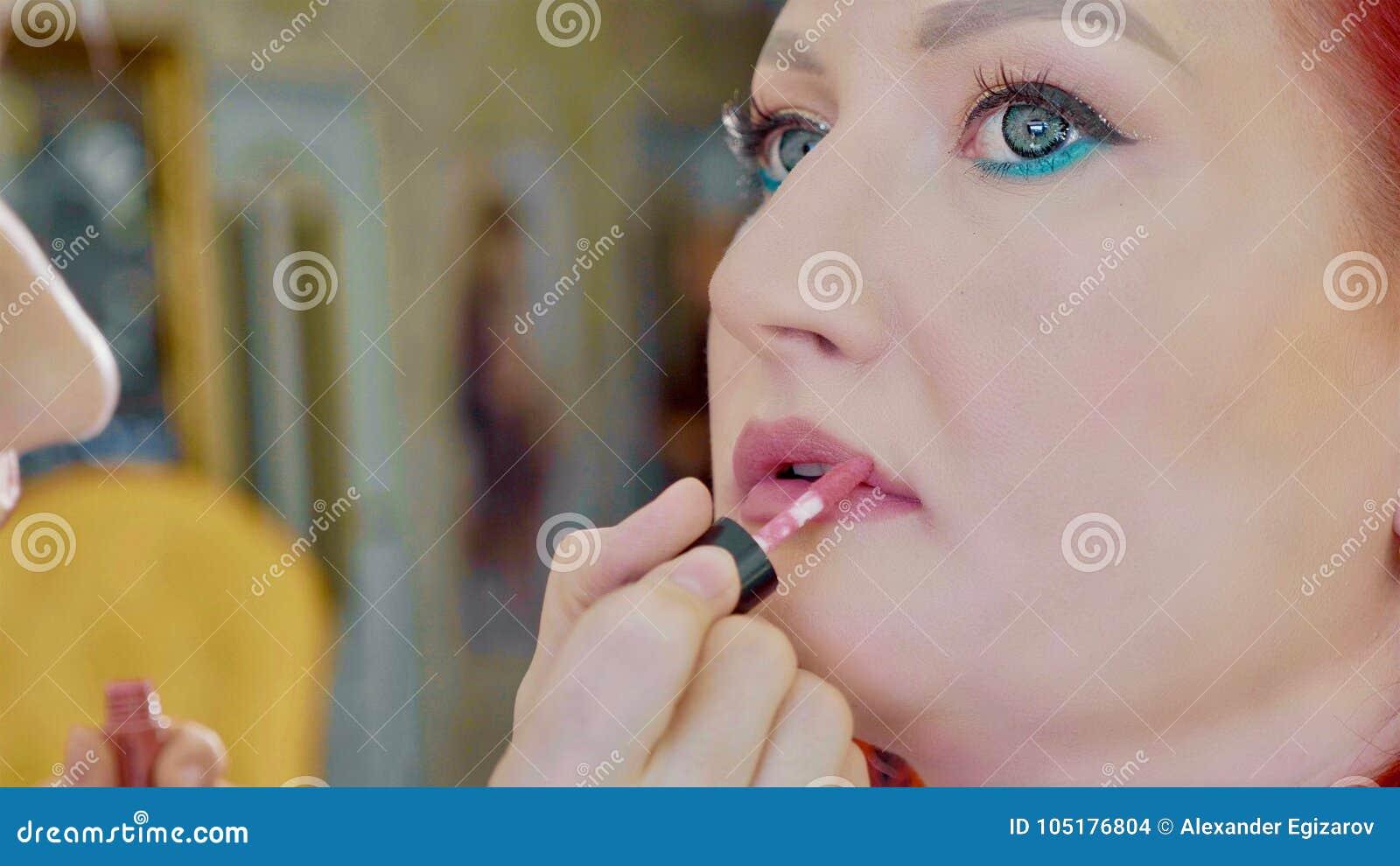 Jeune maquilleur appliquant le rouge à lèvres sur les lèvres modèles du ` s