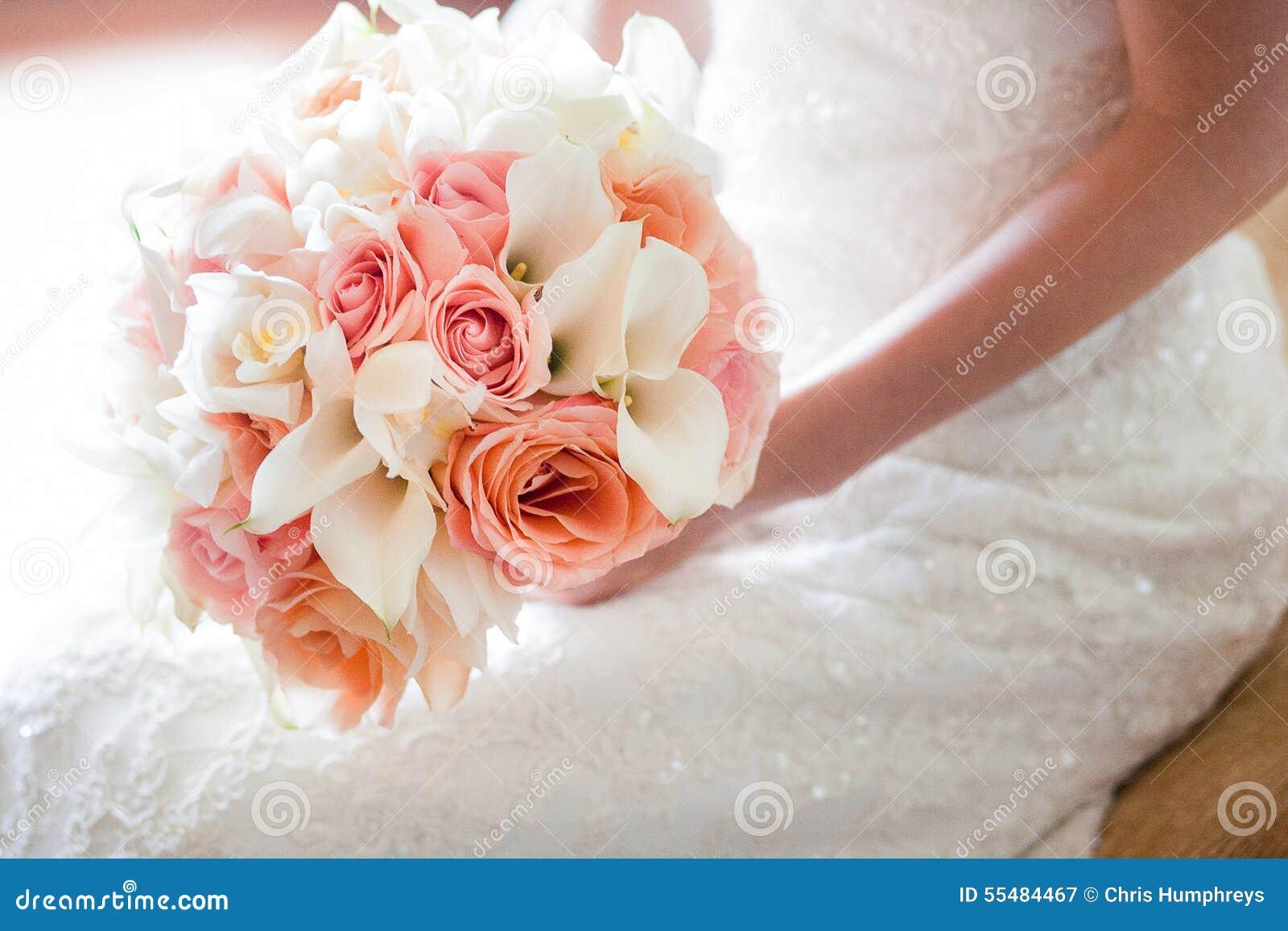 jeune mariée avec le bouquet orange et rose magnifique de mariage