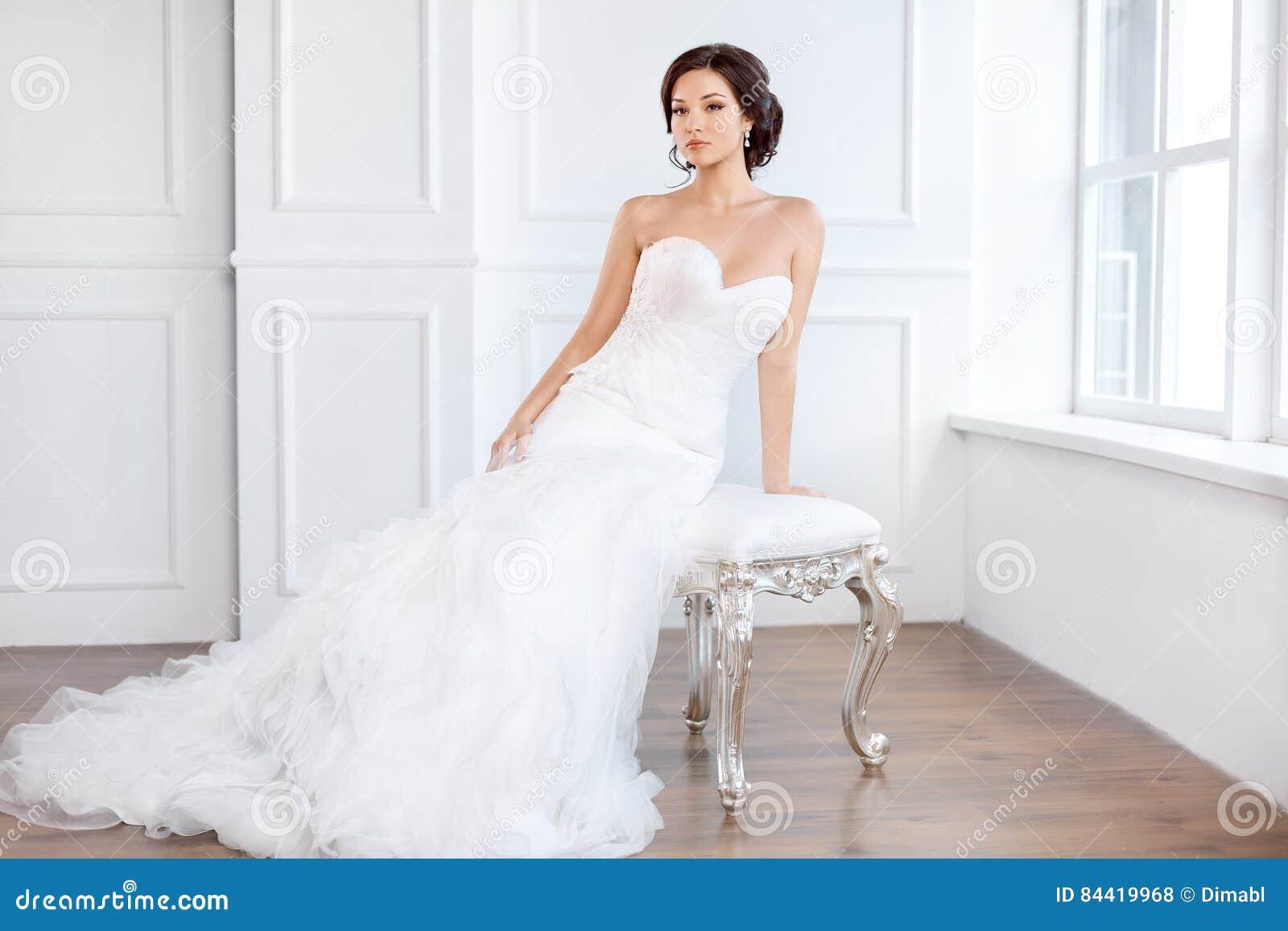 Jeune mariée dans la belle robe se reposant sur la chaise à l intérieur