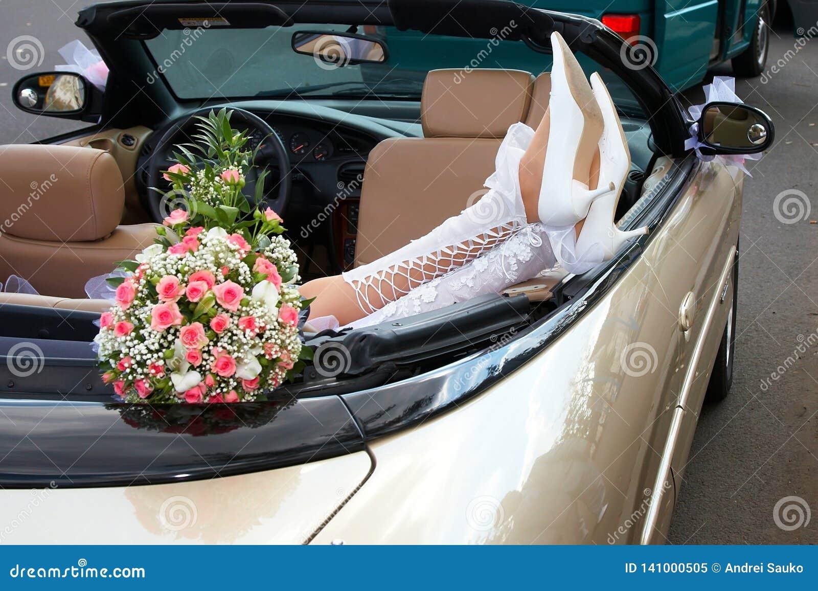 Jeune mariée dans un cabriolet avec des fleurs