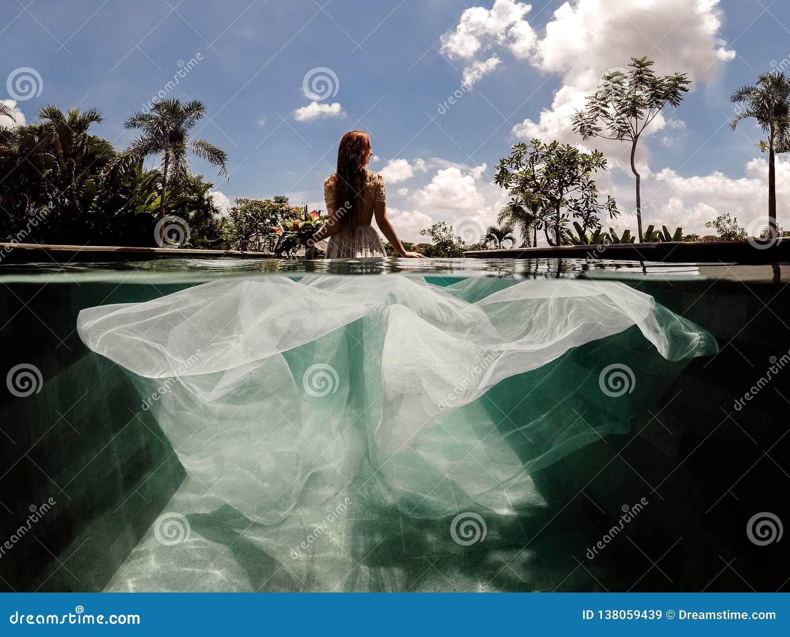 Jeune mariée dans une robe l épousant dans une piscine
