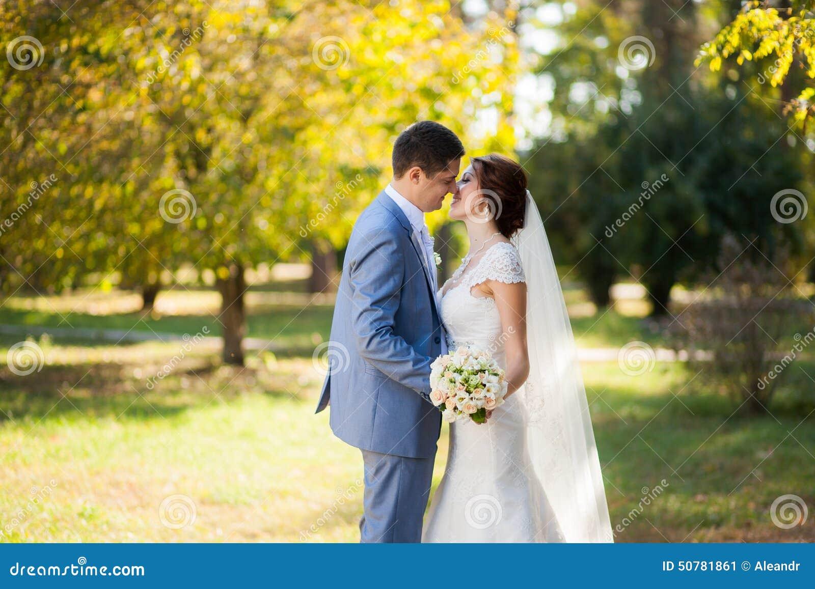 Jeune mariée heureuse, danse de marié en parc vert, embrassant, souriant, riant amants dans le jour du mariage Jeunes couples heu
