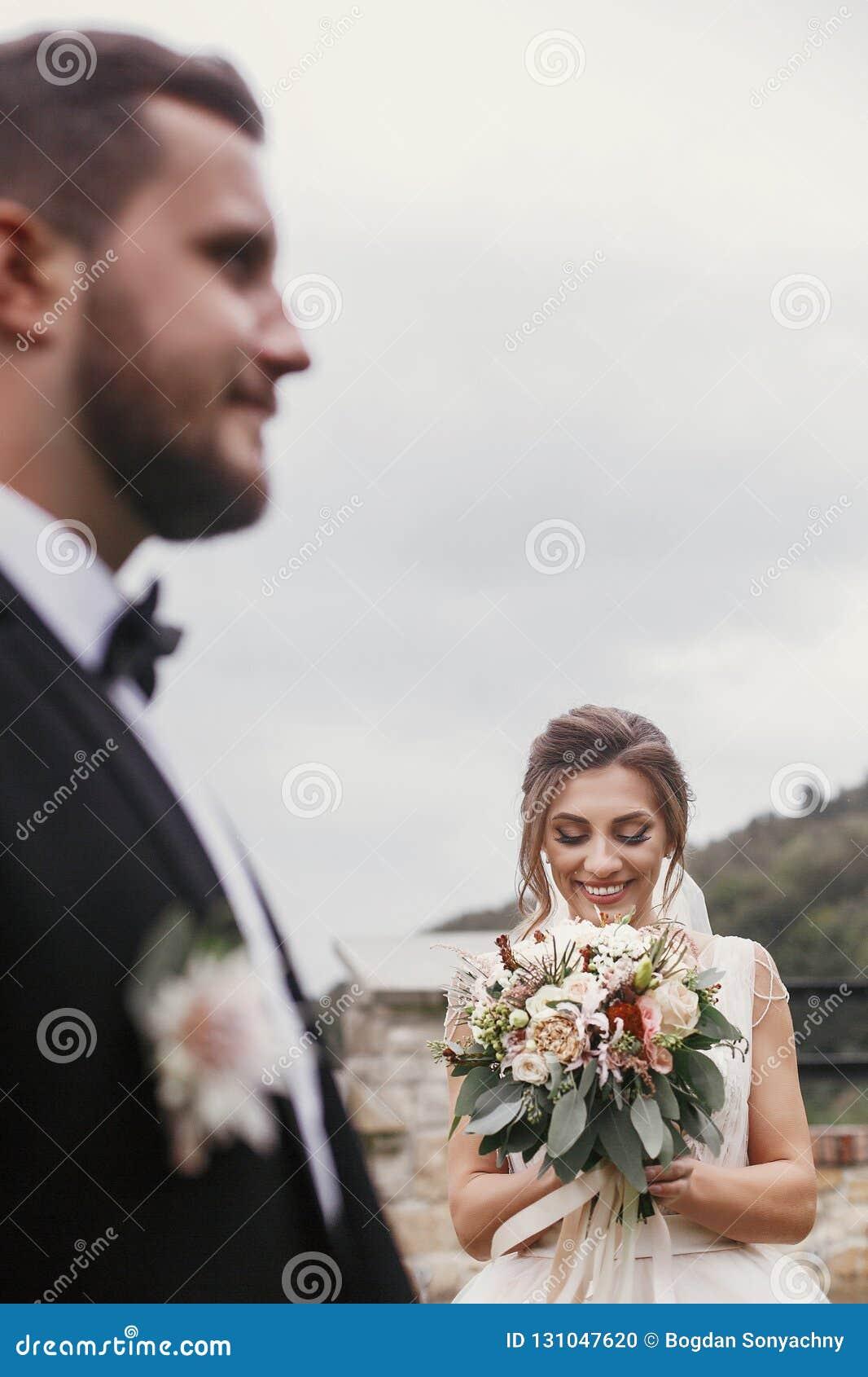 Jeune mariée heureuse magnifique avec le bouquet moderne regardant le groo élégant