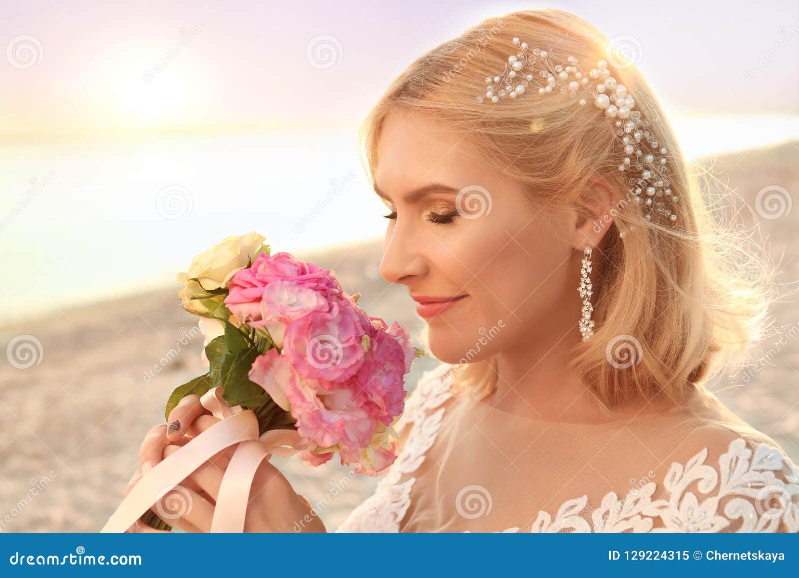 Jeune mariée heureuse tenant le bouquet de mariage
