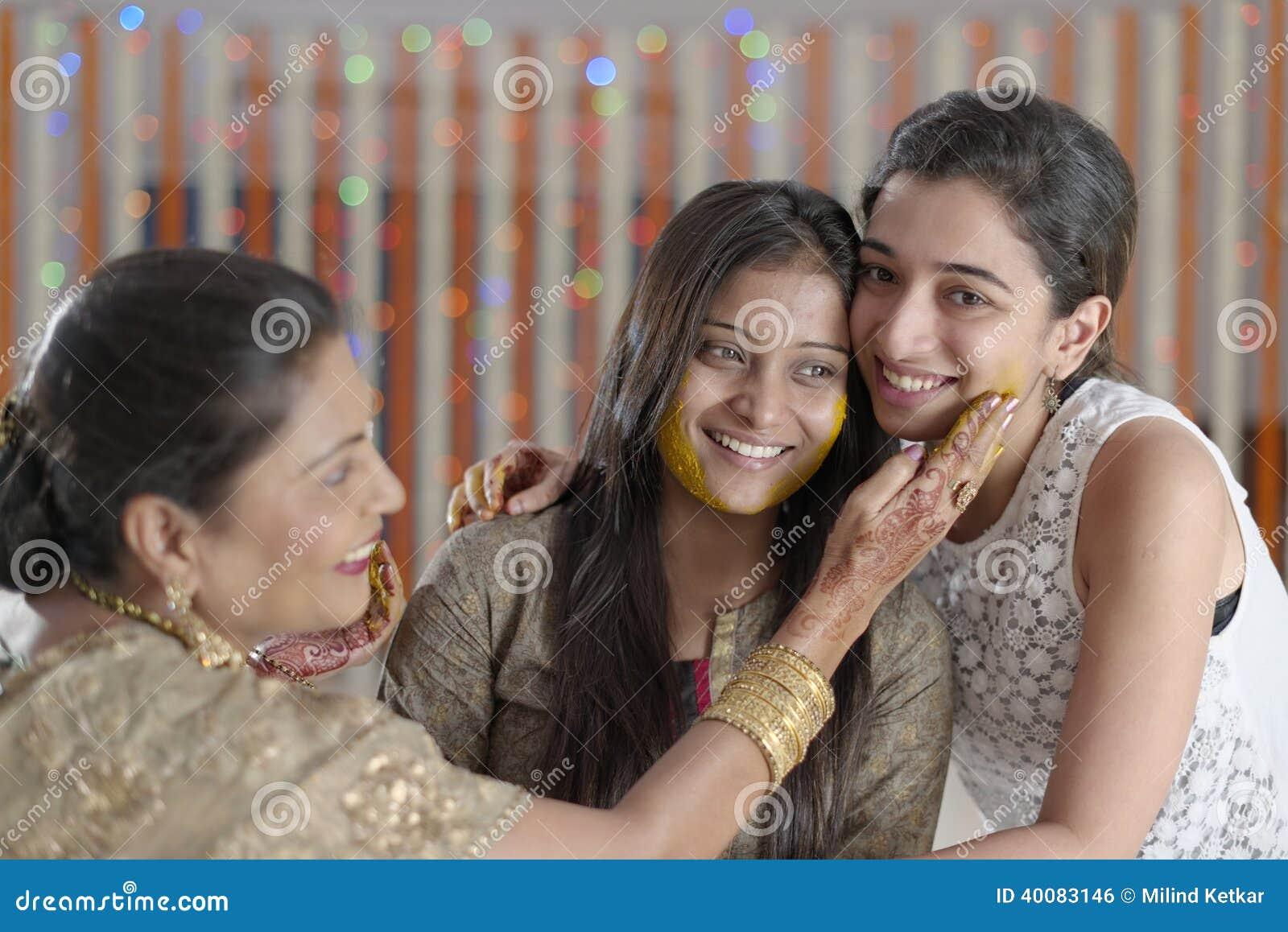 Jeune mariée indoue indienne avec la pâte de safran des indes sur le visage avec la mère et la soeur.