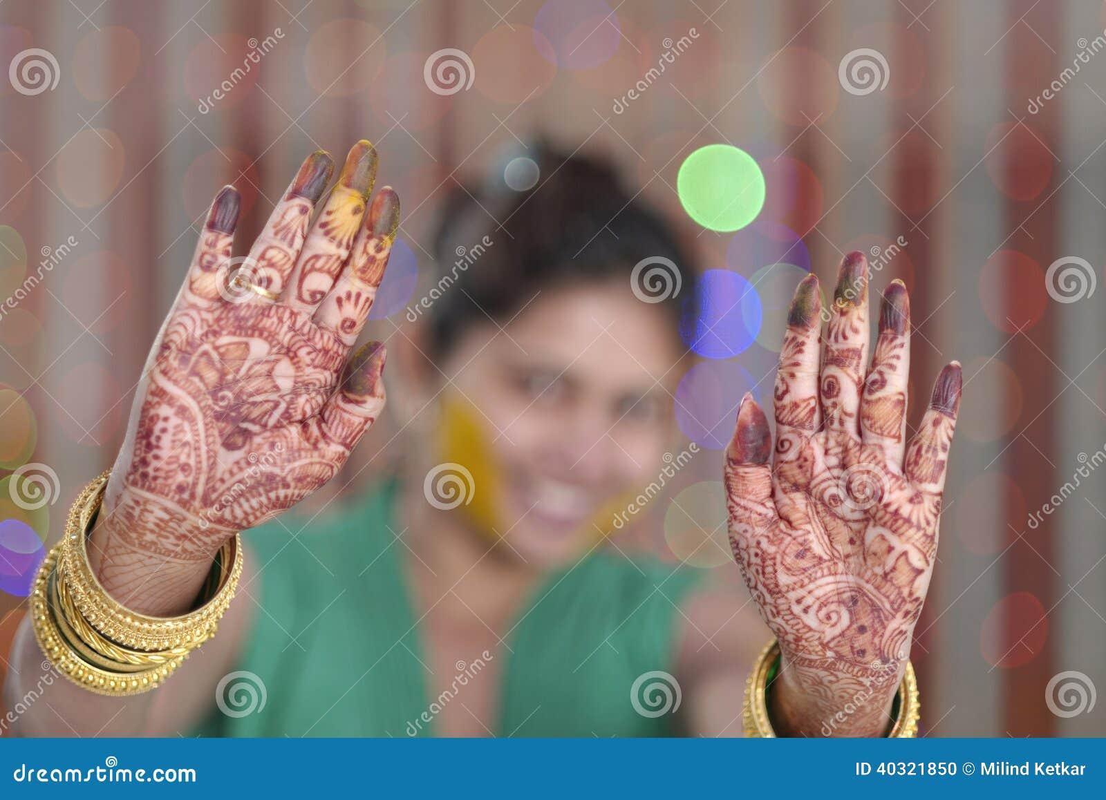 Jeune mariée indoue indienne montrant le henné sur ses paumes.