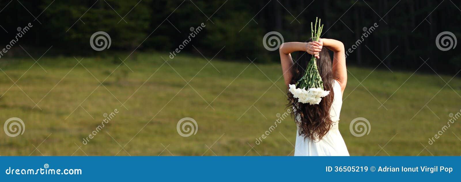Jeune mariée jugeant le bouquet blanc aérien en nature