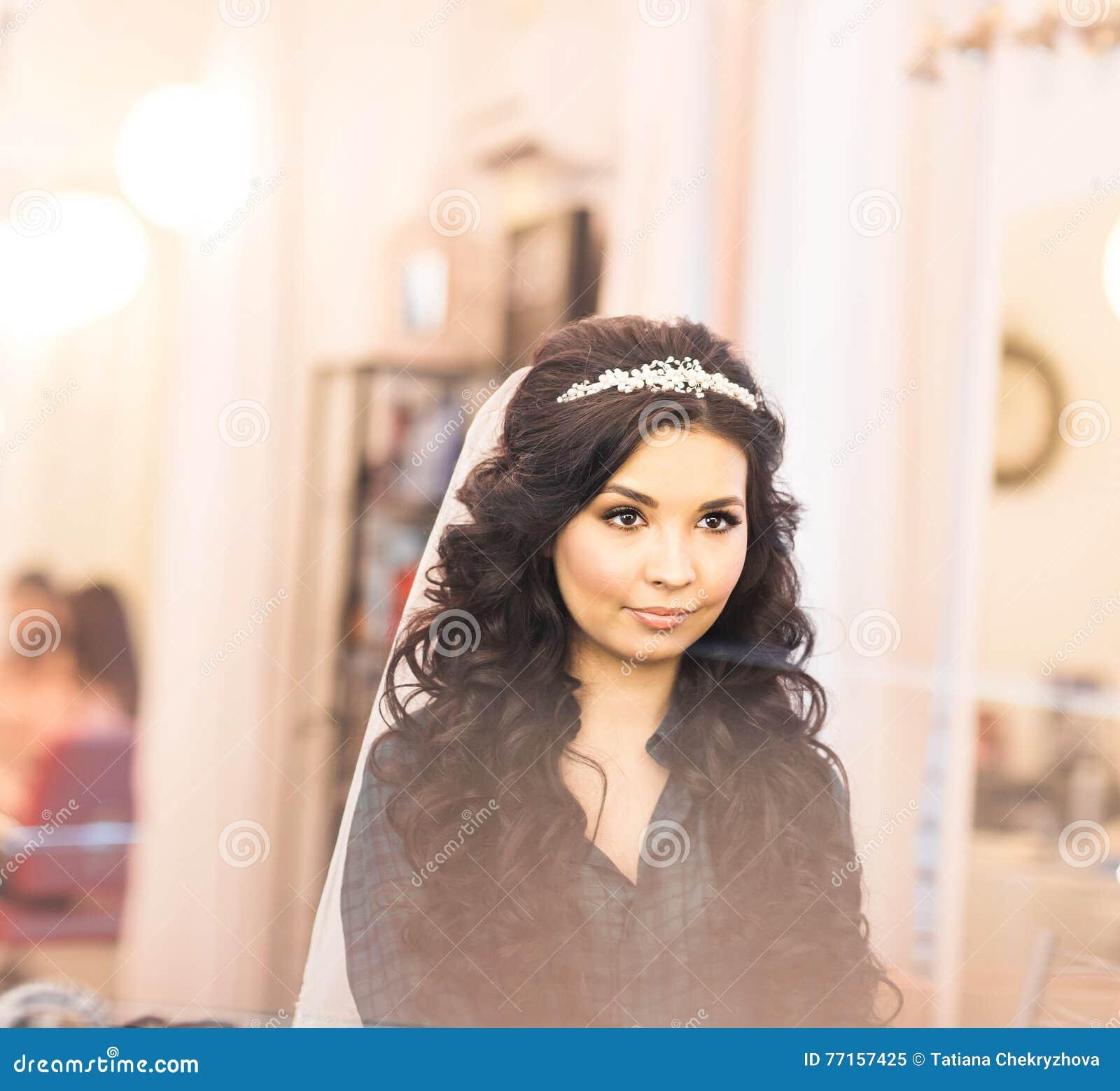 Jeune mariée magnifique élégante obtenant le maquillage dans la salle de luxe de beauté avec de grands miroirs et lumière