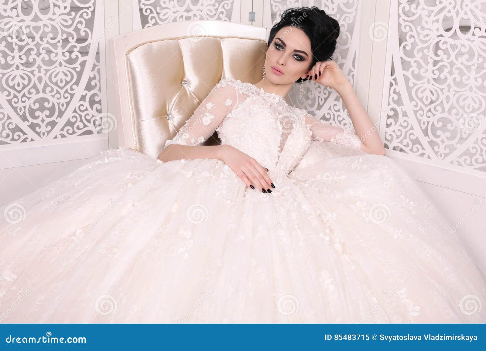 Jeune mariée magnifique avec les cheveux foncés dans la robe de mariage luxuious