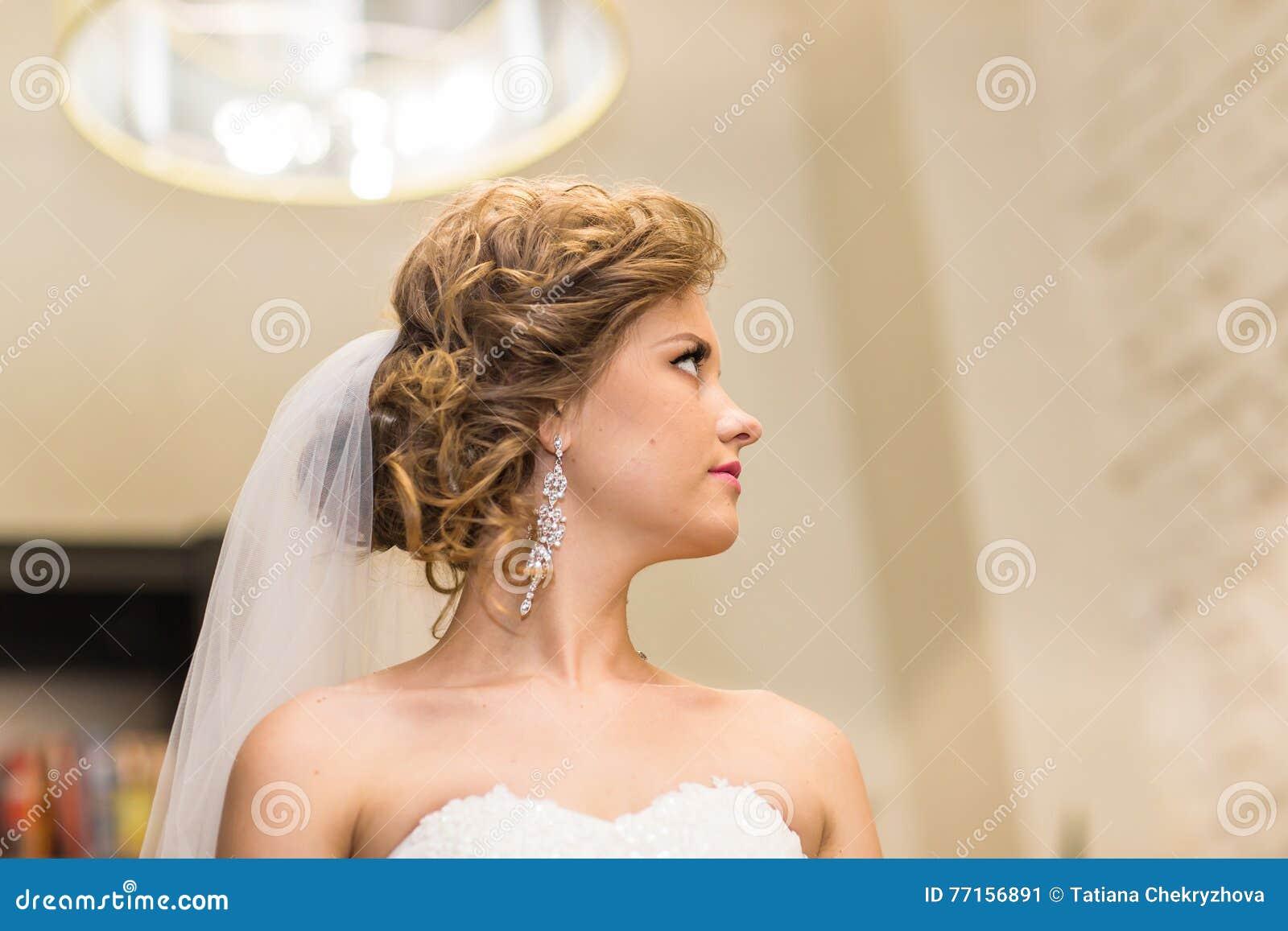 Jeune mariée magnifique dans la robe de mariage avec des bijoux de diamant