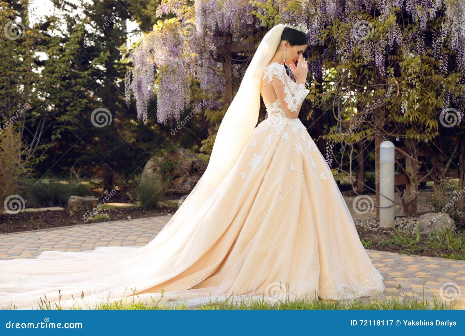 Jeune mariée magnifique dans la robe de mariage luxueuse, posant dans le jardin de fleur