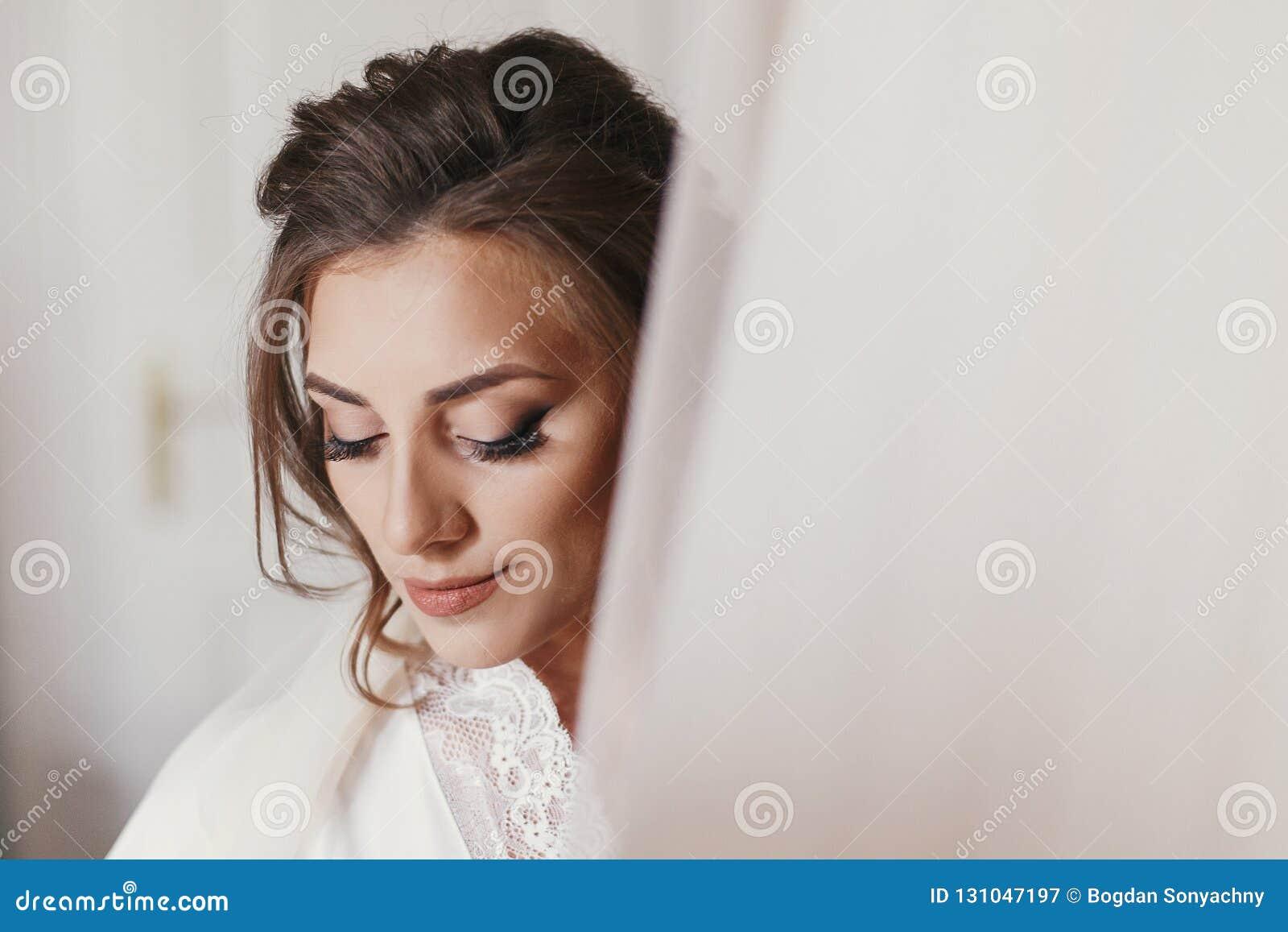 Jeune mariée magnifique dans la robe longue en soie tenant la robe l épousant élégante dans le roo