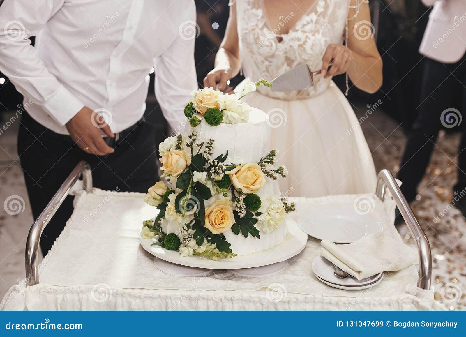 Jeune mariée magnifique et marié élégant coupant ensemble le mariage blanc