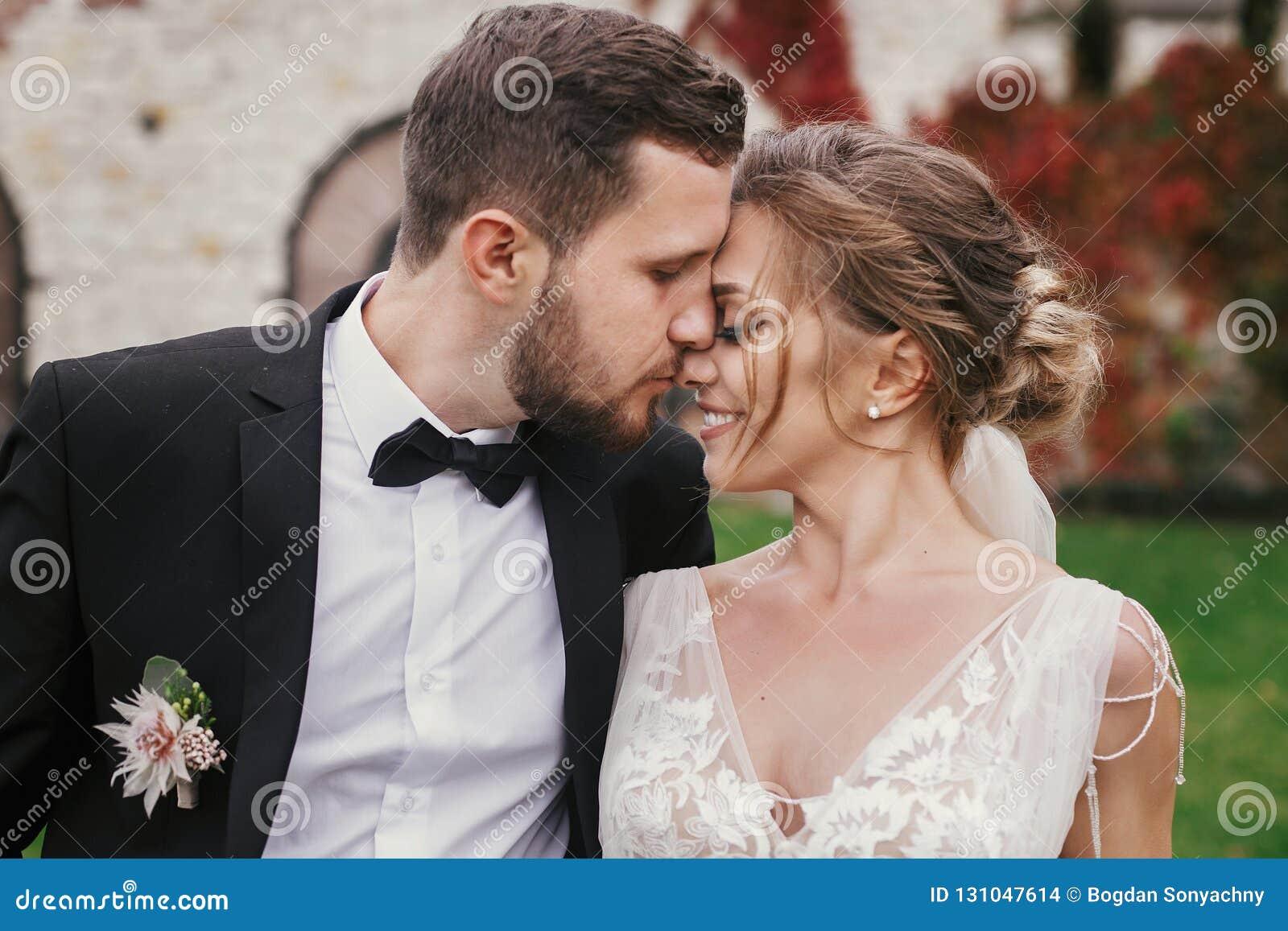 Jeune mariée magnifique et marié élégant doucement étreignant et embrassant l outd