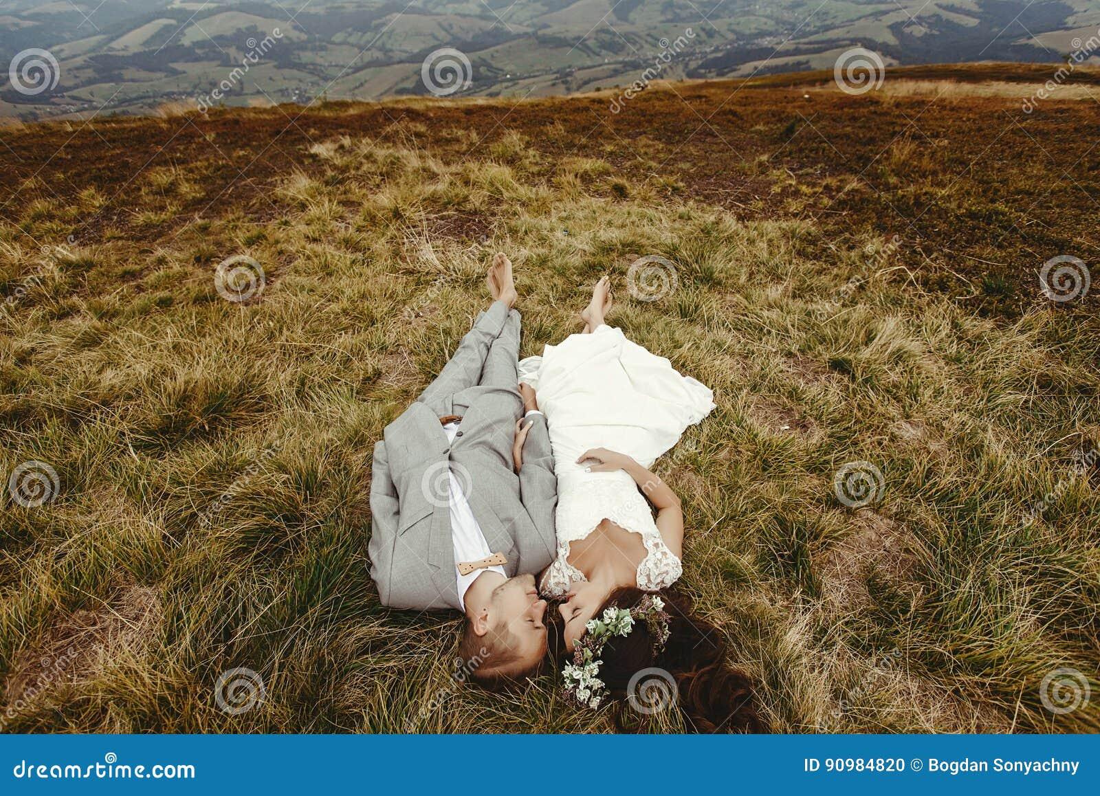 Jeune mariée magnifique et marié élégant se trouvant sur le dessus, cou de mariage de boho