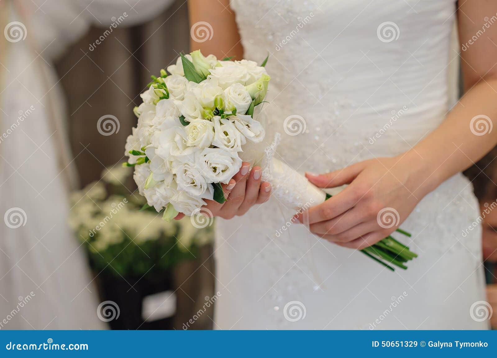 Jeune mariée tenant le bouquet de mariage des fleurs blanches