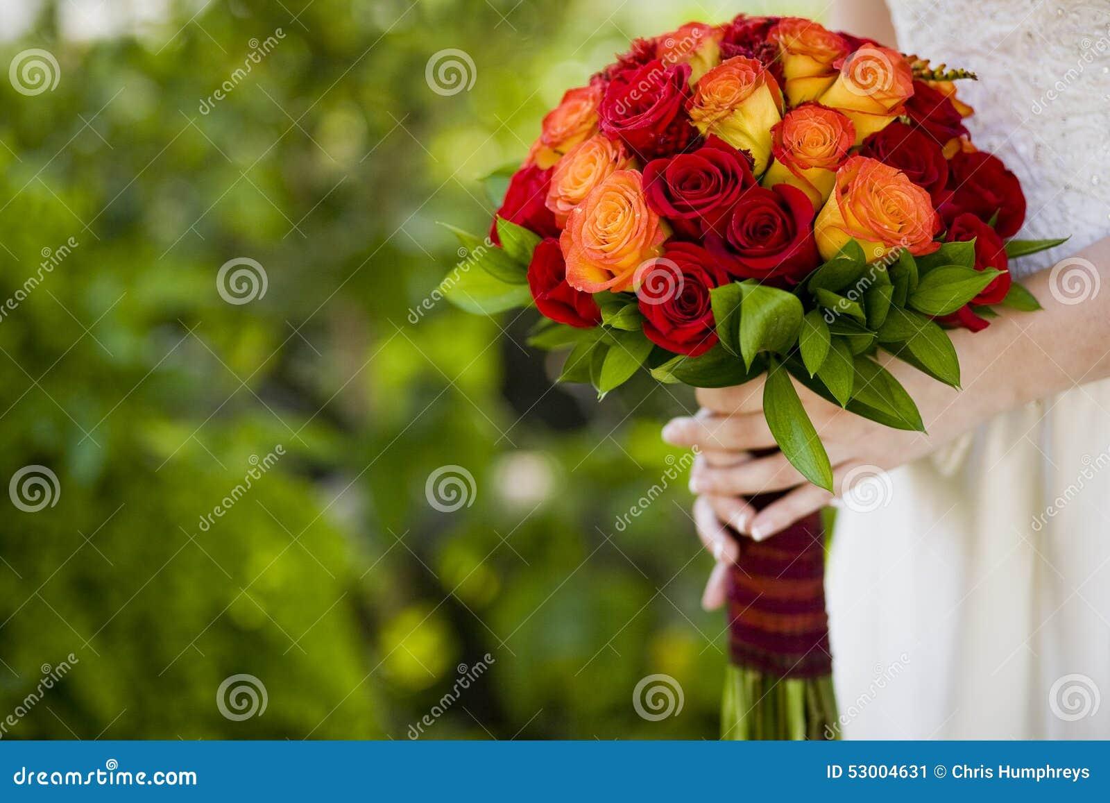 Jeune mari e tenant le bouquet rouge et orange des fleurs for Bouquet de fleurs orange et jaune