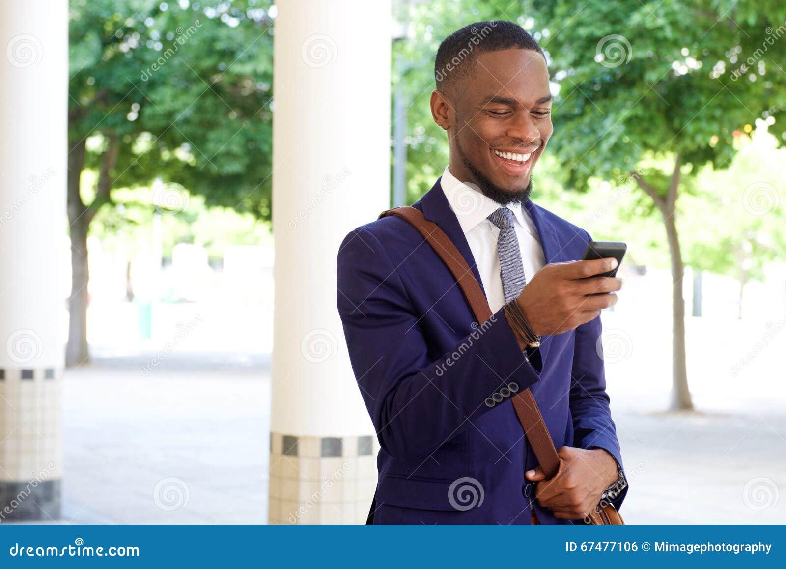 Jeune message textuel heureux de lecture d homme d affaires à son téléphone portable