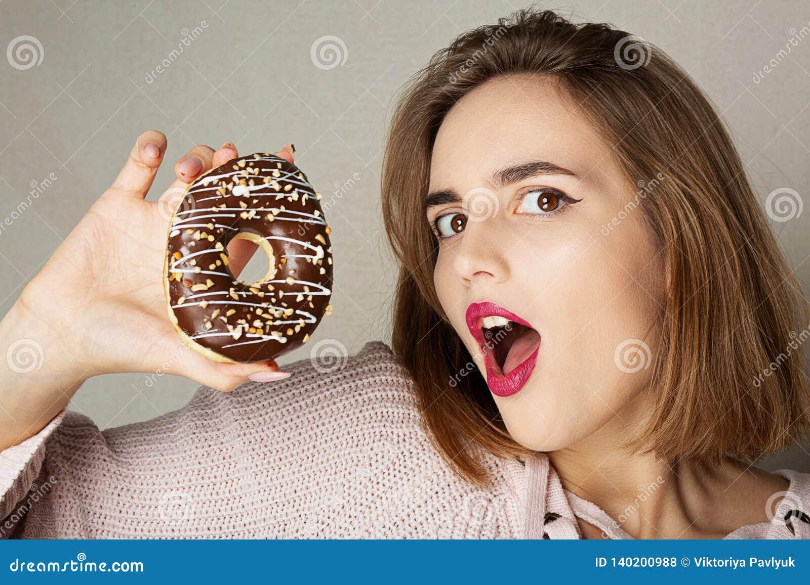 Jeune modèle étonné avec les lèvres roses tenant le beignet de chocolat au-dessus d un fond gris L espace pour le texte