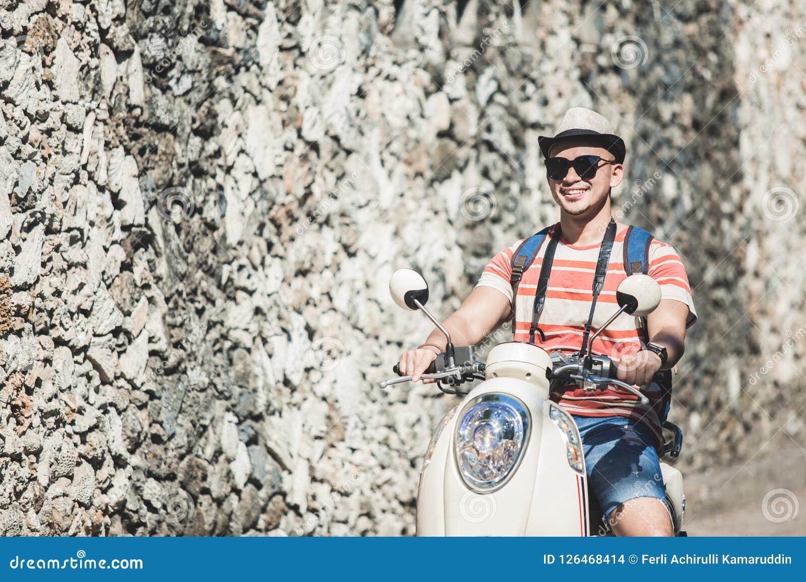Jeune motocyclette d équitation de randonneur pendant des vacances le jour ensoleillé