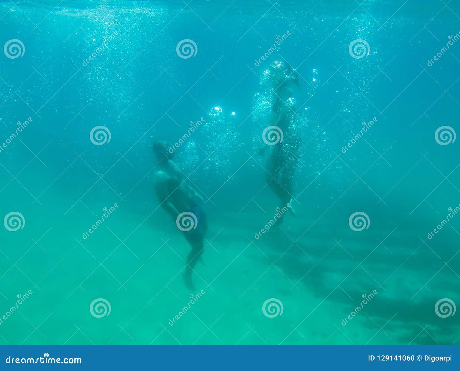 Jeune natation de couples dans une eau transparente d océan en Espagne
