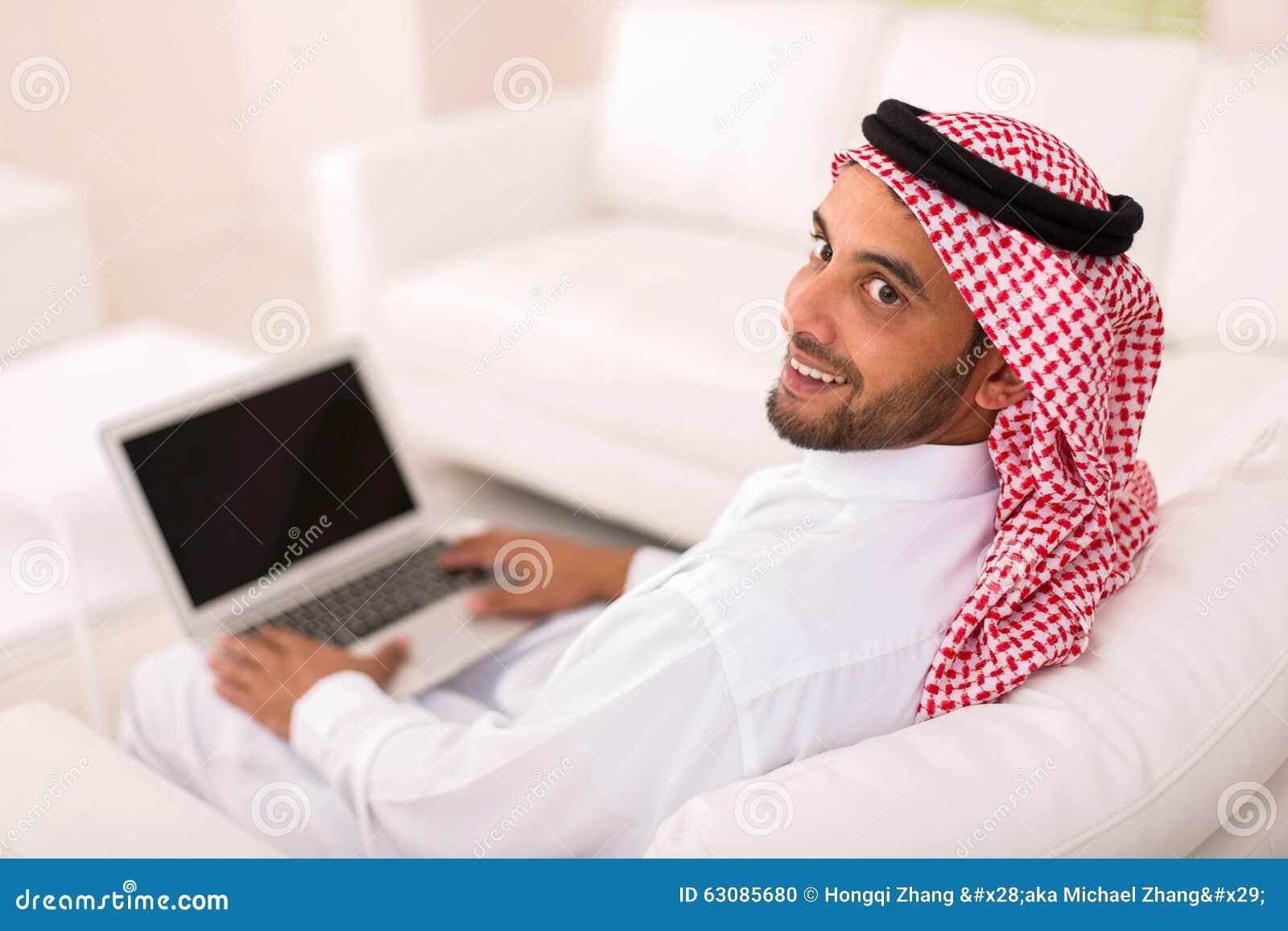 Download Jeune Ordinateur Portable Arabe D'homme Photo stock - Image du pose, divan: 63085680