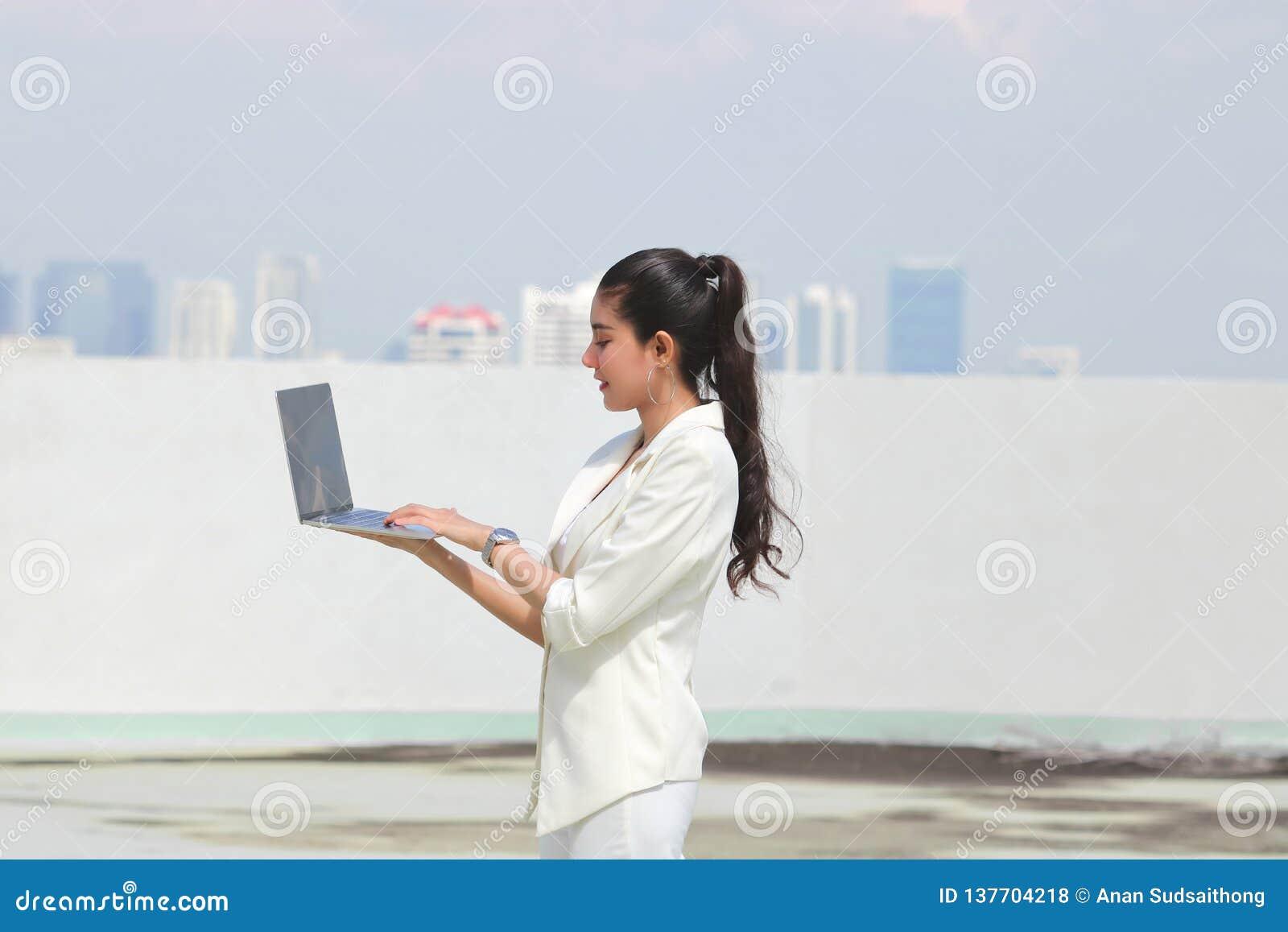 Jeune ordinateur portable asiatique sûr de participation de femme d affaires avec des mains E