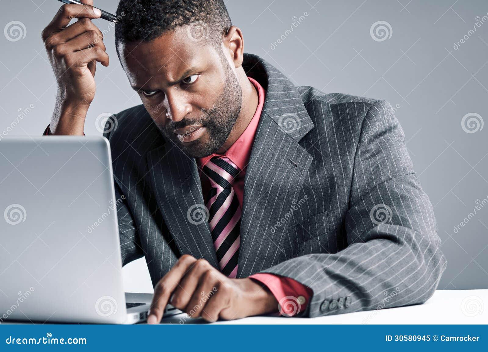 Jeune ordinateur portable de Being Sneaky On d homme d affaires d Afro-américain