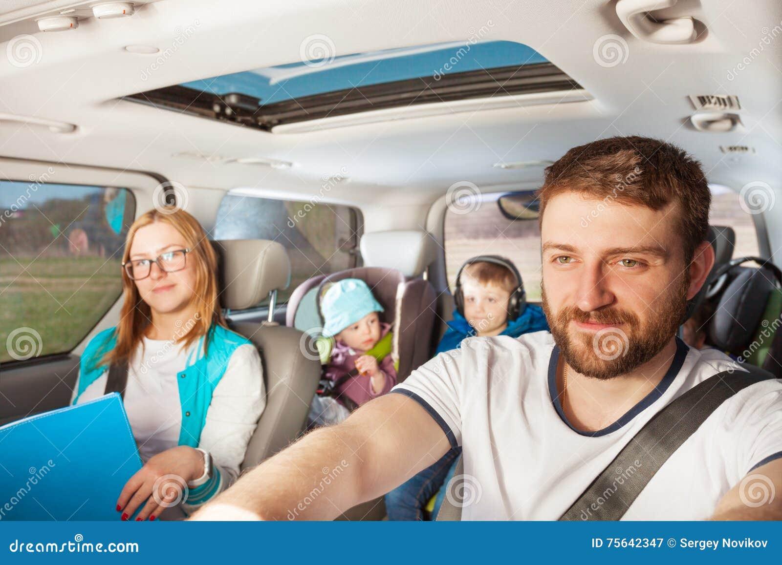 Jeune père conduisant sa voiture familiale