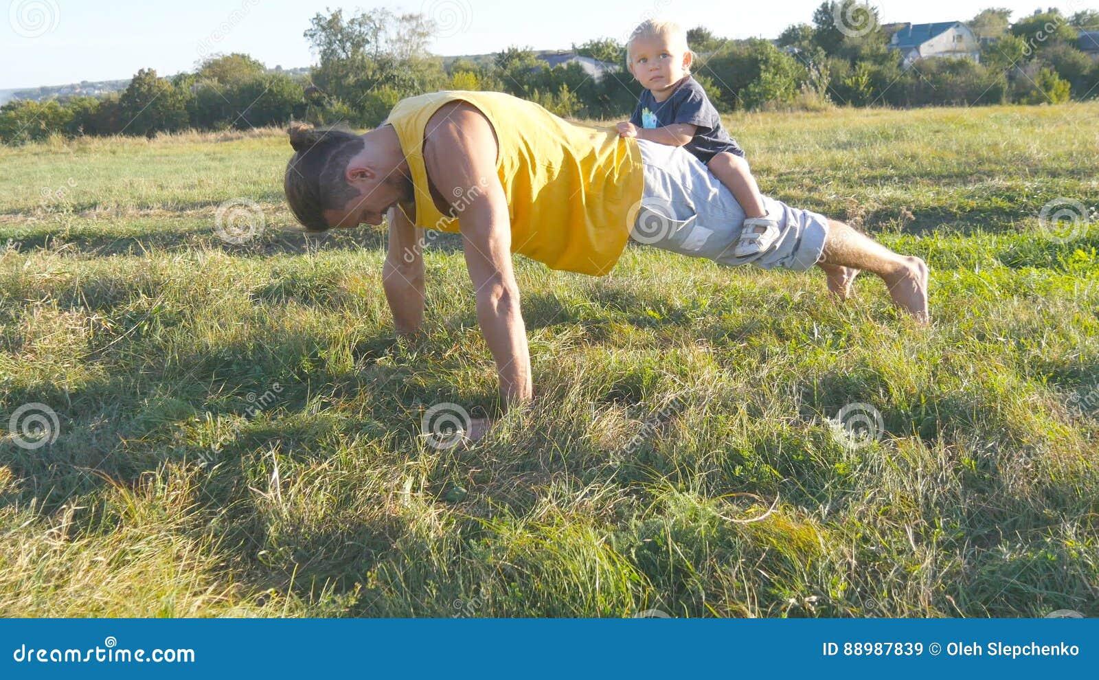 Jeune père musculaire faisant des pousées avec son petit fils sur le sien de retour Homme sportif faisant des pousées à l herbe v