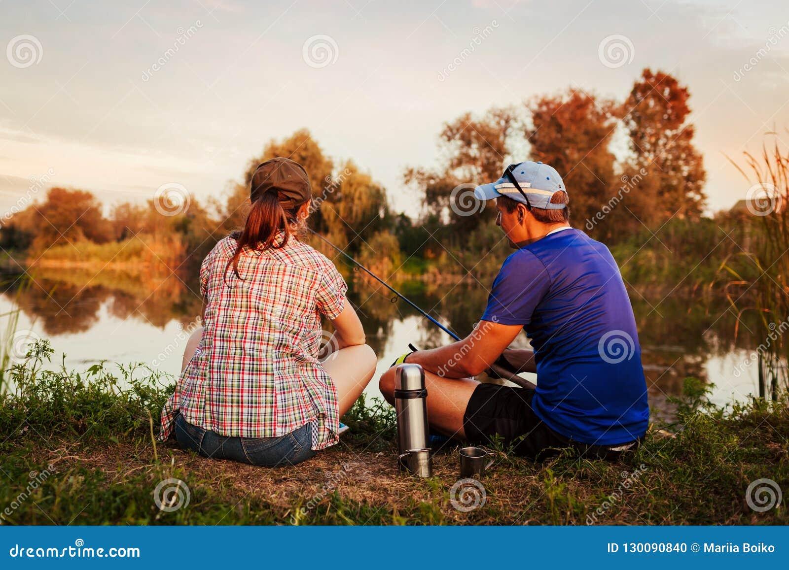 Jeune pêche de couples et thé potable sur la rivière au coucher du soleil Les gens détendant et refroidissant dehors
