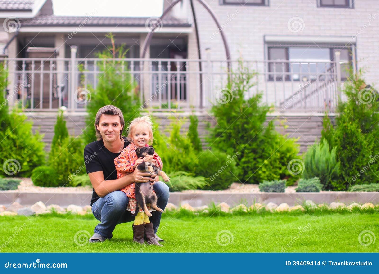 Jeune papa et sa petite fille avec son chiot sur le fond leur maison