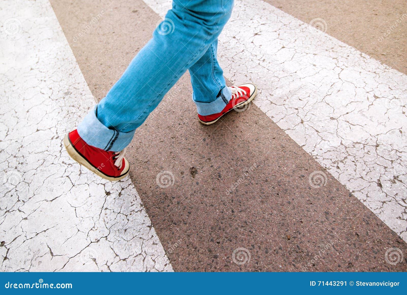 Jeune personne adolescente marchant au-dessus du passage piéton piétonnier de zèbre