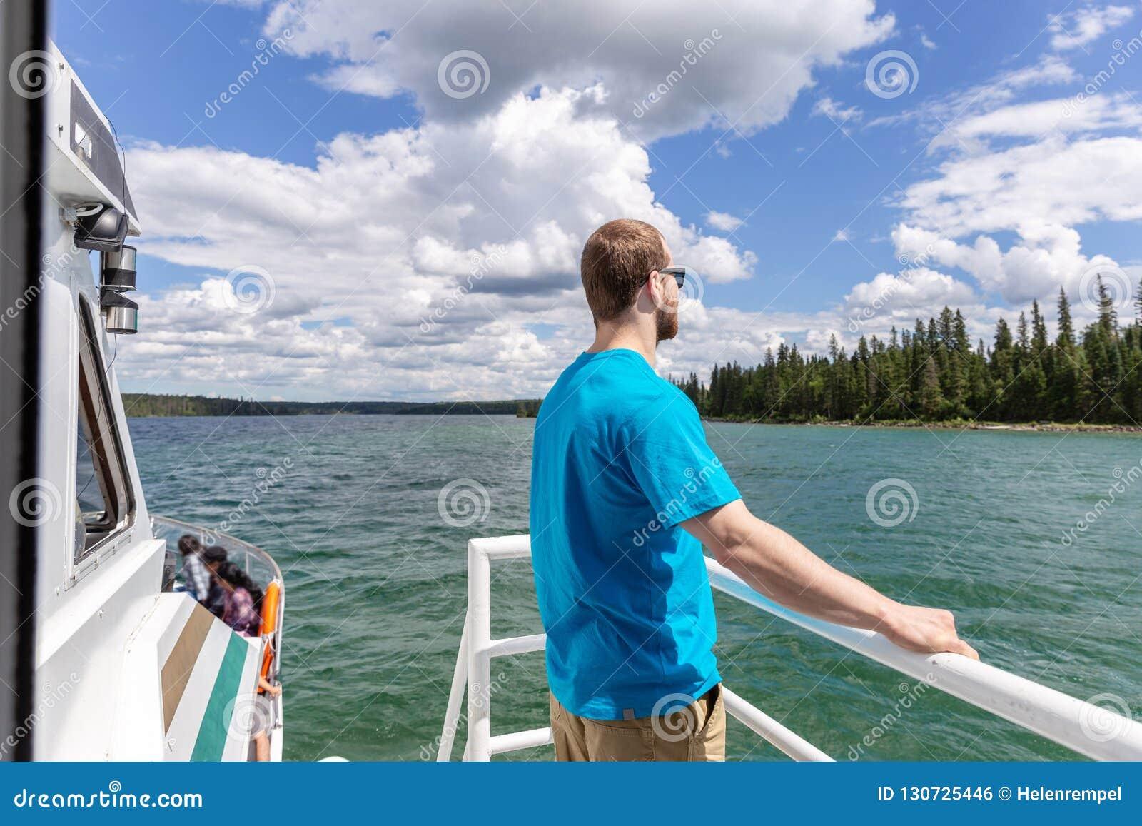 Jeune position attrayante d homme sur la plate-forme du bateau sur le lac