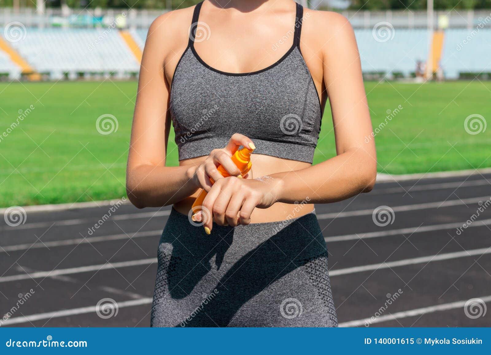 Jeune position femelle de coureur et mise de la lotion du soleil en main Fille employant le sunscream avant exercice courant de s