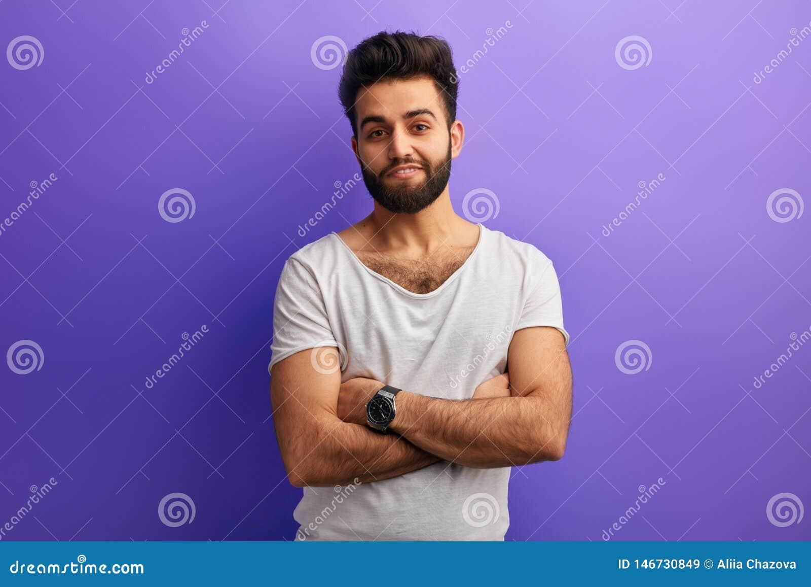 Jeune position indienne barbue d homme avec les bras croisés sur le fond bleu
