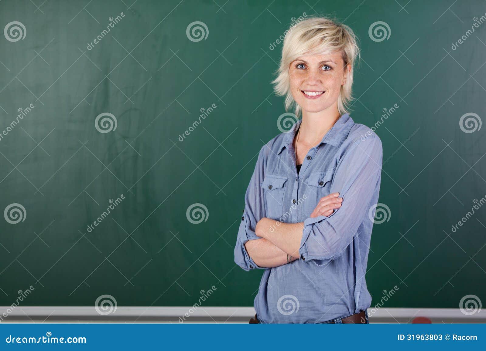 Jeune professeur féminin sûr In Front Of Chalkboard