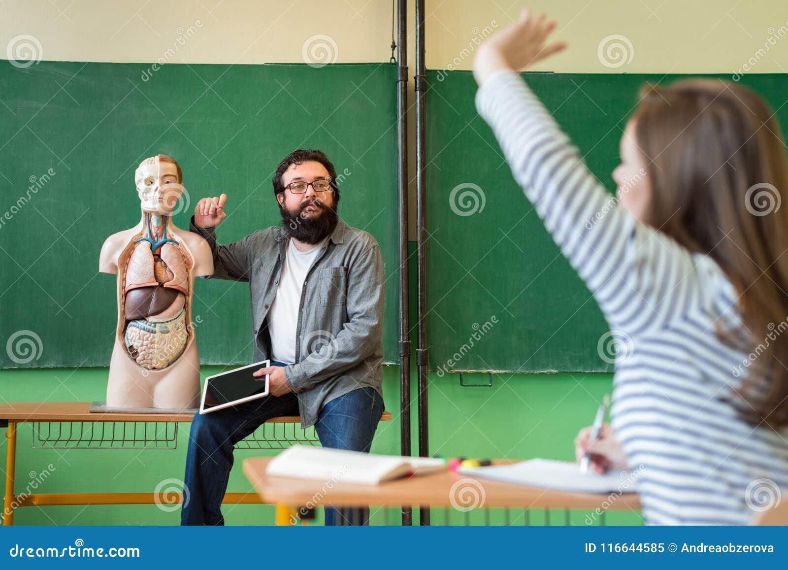Jeune professeur hispanique masculin dans le cours de Biologie, tenant le comprimé numérique et enseignant l anatomie de corps hu