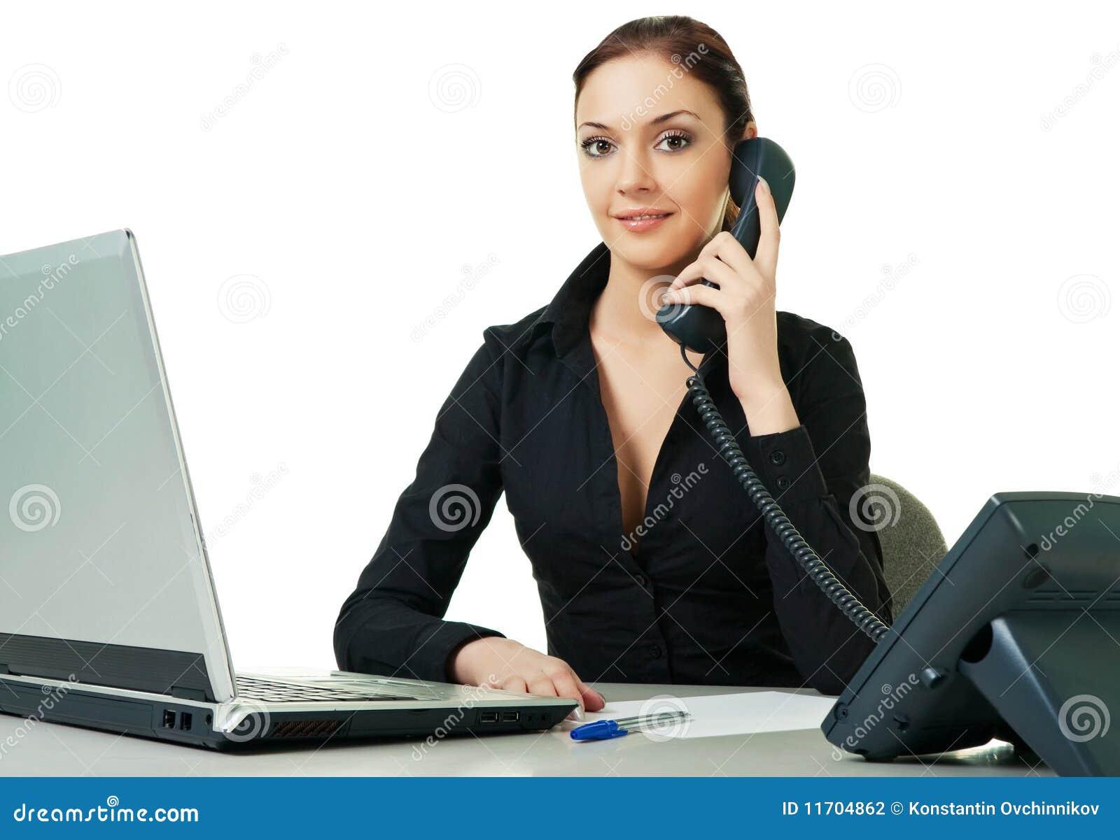 Jeune réceptionniste de sourire à l aide du téléphone de bureau