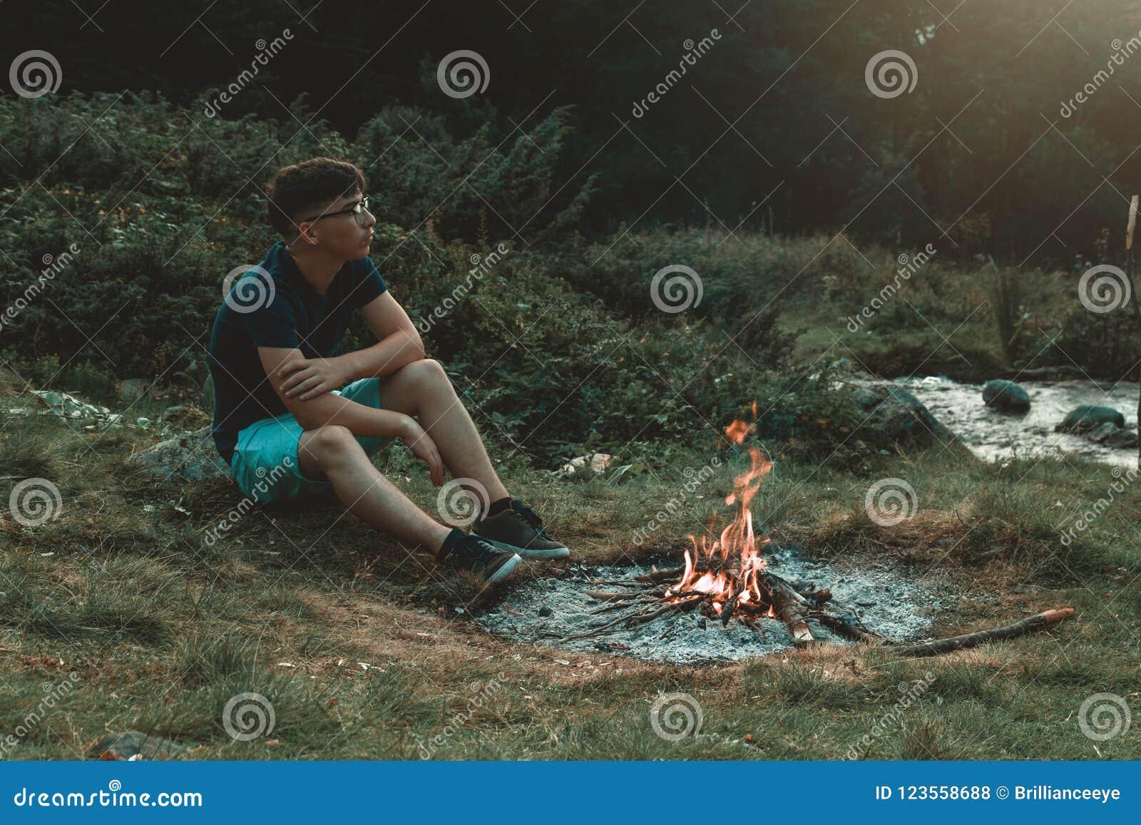 Jeune randonneur s asseyant à côté de la cheminée et le feu et la pensée