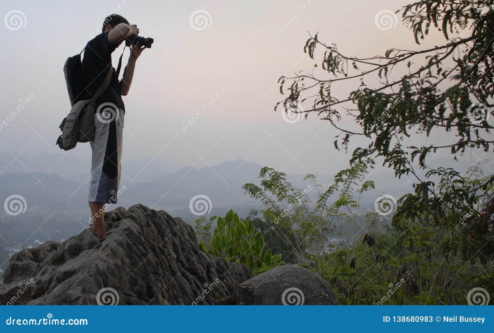 Jeune randonneur, voyageur prenant des photos au coucher du soleil, sommet de Luang Prabang
