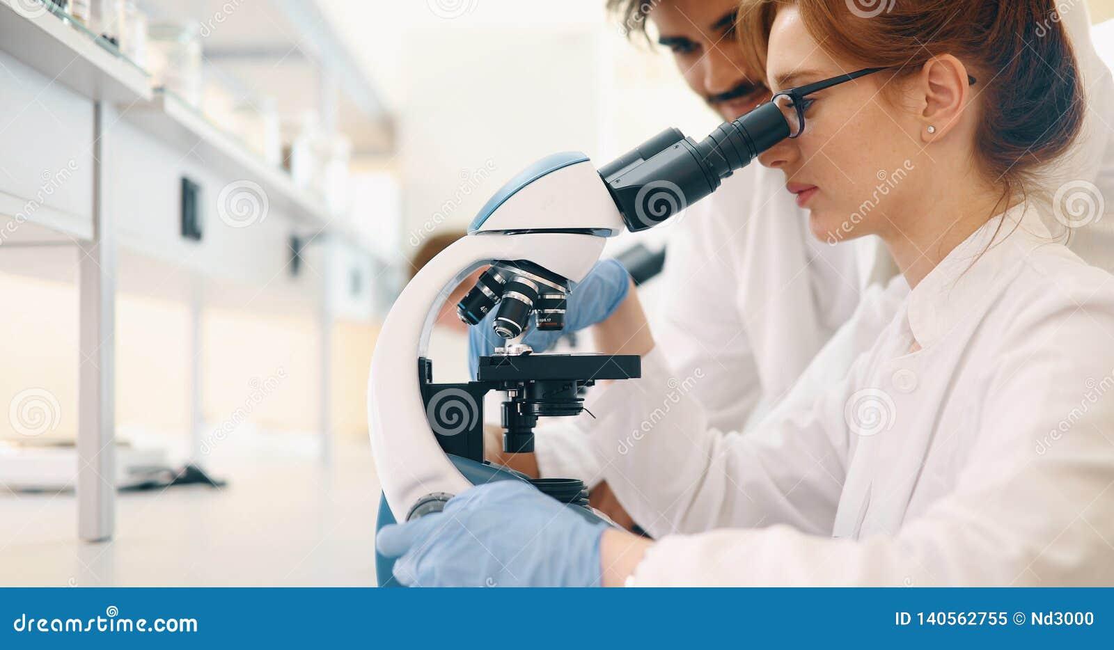 Jeune scientifique regardant par le microscope dans le laboratoire