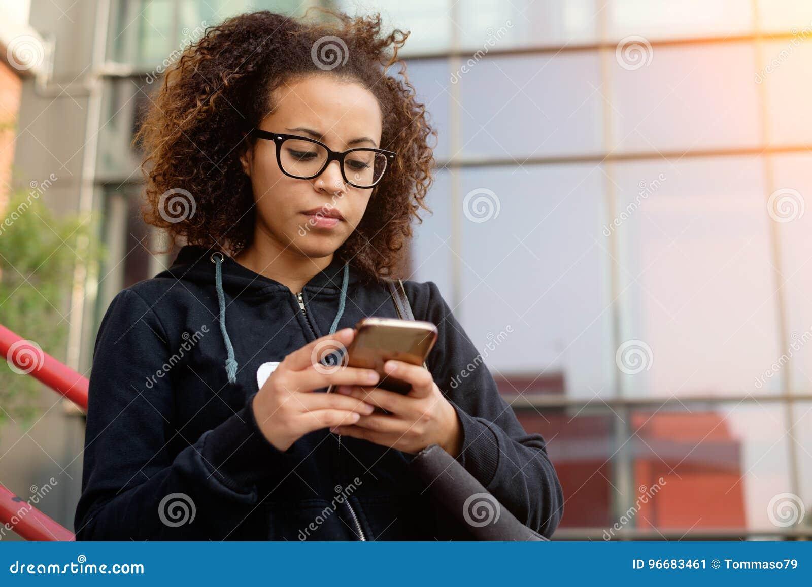 Jeune service de mini-messages millénaire de fille à son téléphone